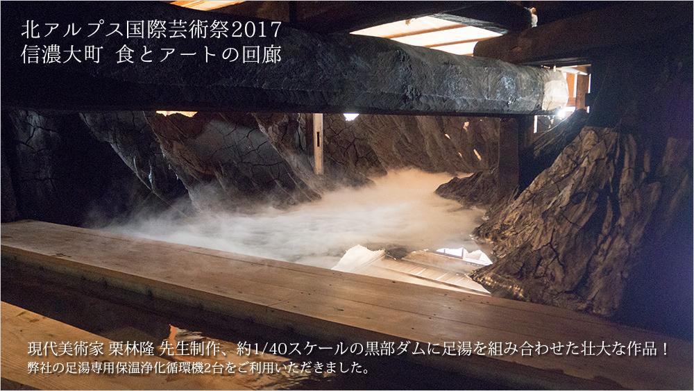 """国際的な現代美術家の栗林 隆先生は、""""世紀の大事業""""と謳われた黒部ダムを約1/40スケールで再現。この黒部ダムに足湯を組み合わせた壮大な作品を、商店街の空き店舗内部に制作しました。弊社の足湯専用保温浄化循環機2台をご利用いただき、2ヶ月間の開催期間中にお越しいただいた約2,000名のお客様に大好評でした。"""